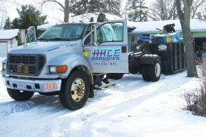 Aace junk removal services truck and roll-off dumpster at garage junk removal project